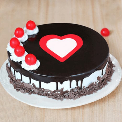 round-black-forest-cake-with-heart-in-center-and cherries-on-top