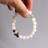 White bodhi seed bracelet with carved flower and jade accents - held by model