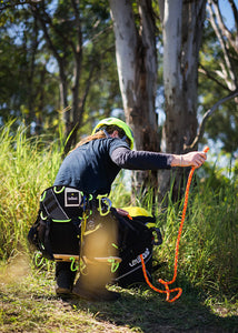 Image of arborist bending down over Courant rope bag and pulling out the Komora rope, a bright orange rope. Arborist is wearing Koala harness and Singing Rock flash aero helmet.