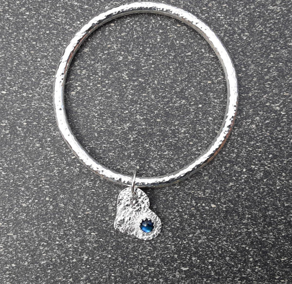 Chunky hammered sterling silver bangle with gemstone heart charm