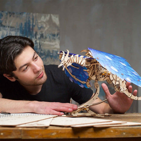 Man playing with wooden model dragon