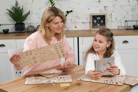 women and girl sorting parts of wooden mechanical model kit