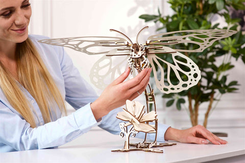 women playing with completed wooden butterfly model kit