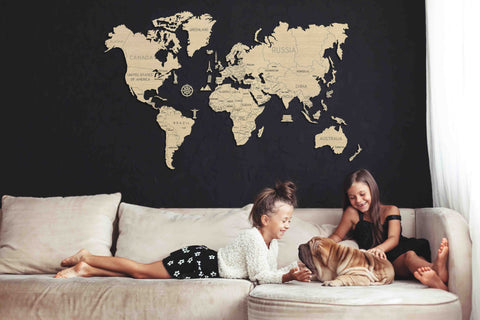 Mother and daughter on a couch while displayed on the wall above is a wooden world map puzzle kit