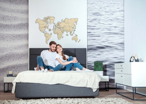 A couple sitting on their bed and overhead is a wooden world map puzzle kit