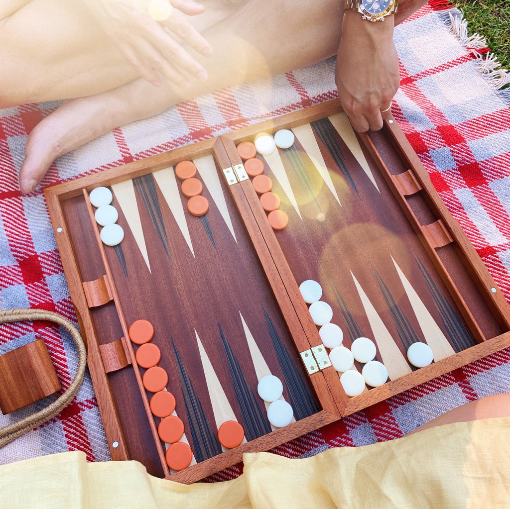 A wooden backgammon board sits atop a checkered picnic blanket. A yellow dress is visible on the bottom of the image and a hand coming into the frame is also visible as well as a ray of sunshine.
