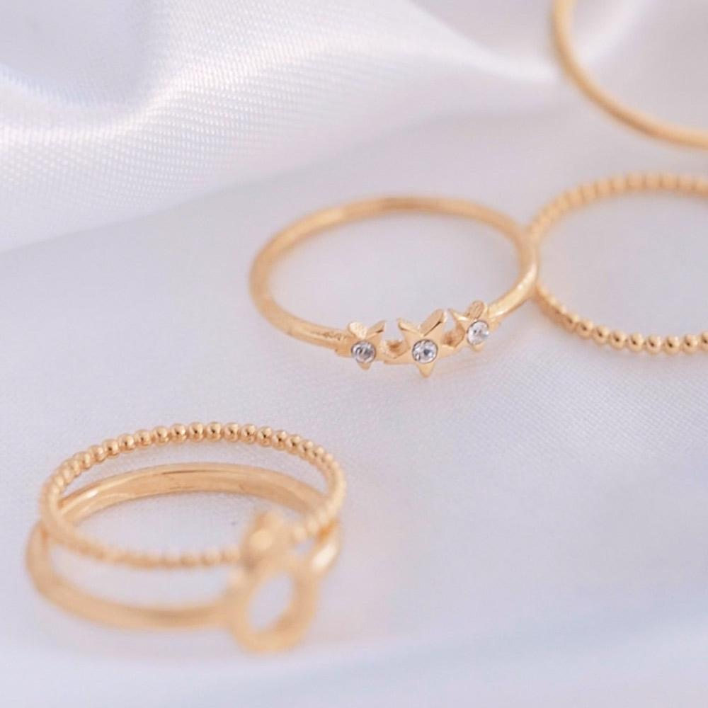 Katie Dean rings on white material background.