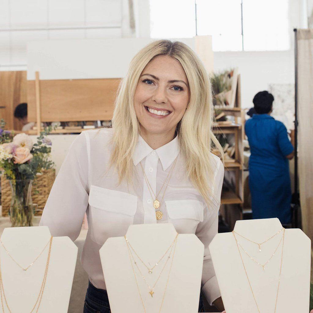 Katie Dean, founder and designer of Katie Dean Jewelry, smiling at the camera at her Renegade Craft Fair booth in San Francisco