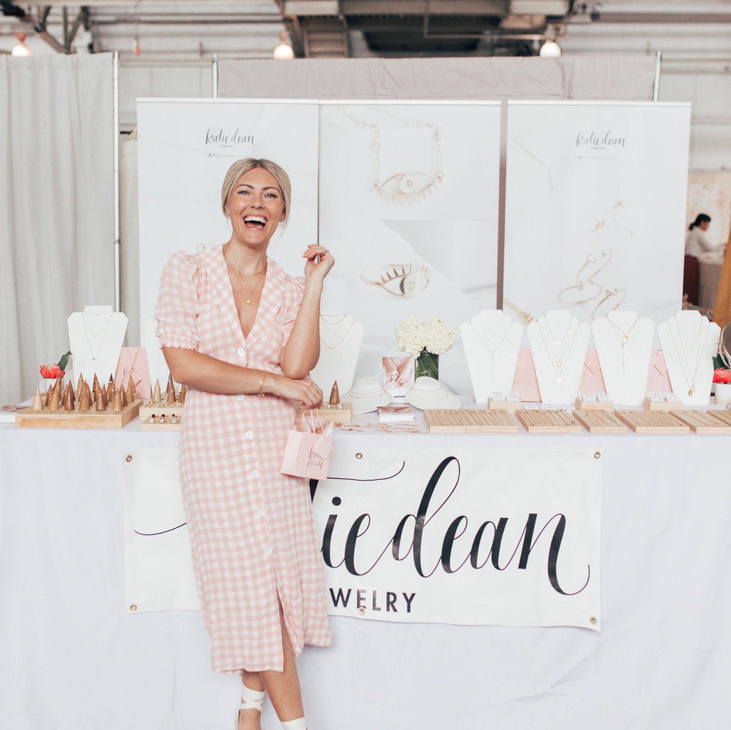 Katie Dean, founder of Katie Dean Jewelry at Renegade Craft Fair, standing in front of her display of handmade dainty jewelry.