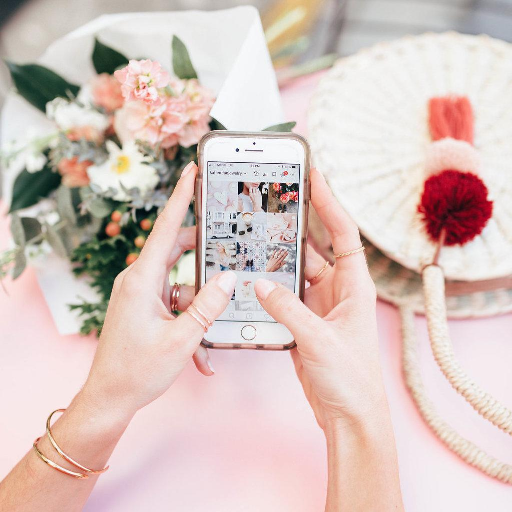 Two hands holding iphone showing Katie Dean Jewelry Instagram with flowers and straw bag on pink table. Gold rings and bangles on hands and wrists.