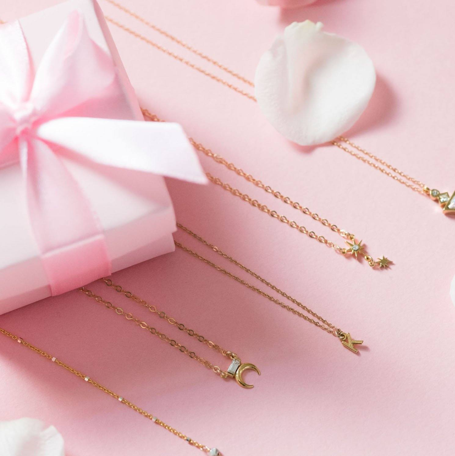 Katie Dean Jewelry on pink flat lay with pink box with pink bow.