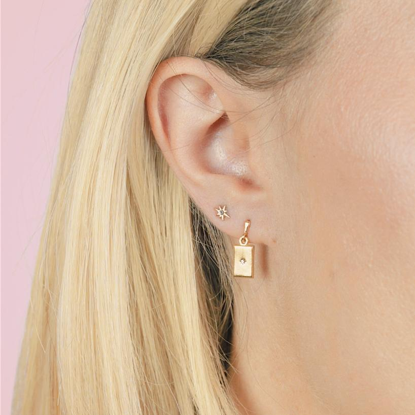 Close up of a dainty star earring and rectangle earring on a models ear.