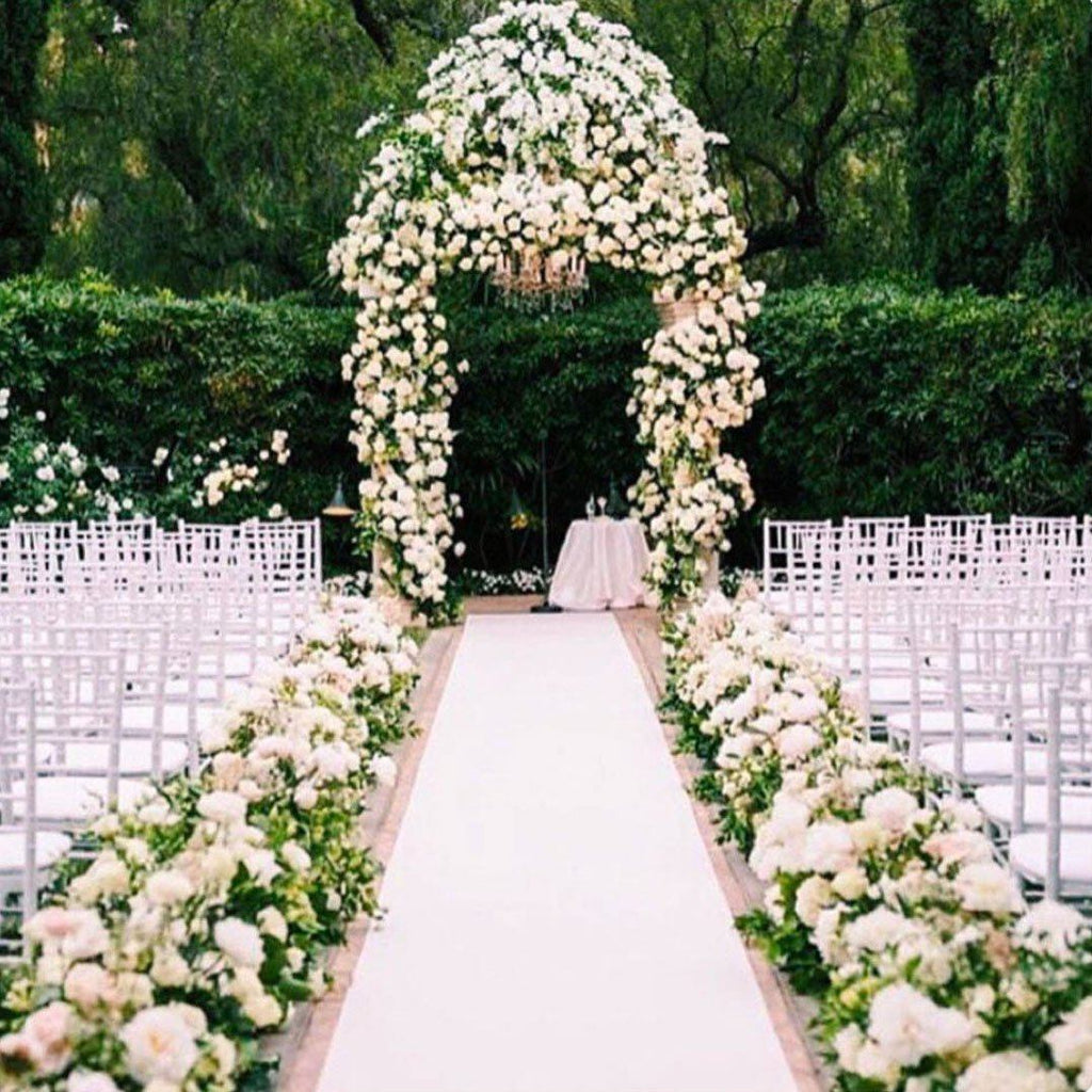 Wedding isle with a white center isle and each side flanked by white and green floral arrangmenets.