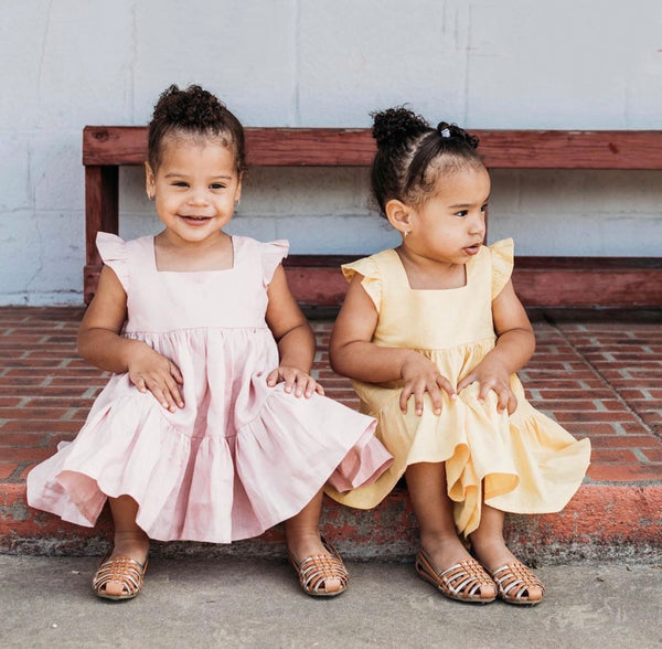 Two little girls in a pink linen dress and a yellow linen dress by Ava and Isa