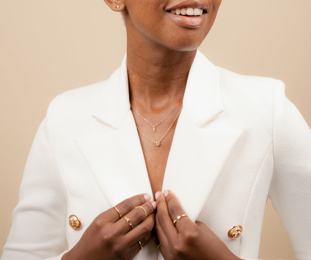 Picture of a model wearing the dainty gold necklaces, featuring the Initial Necklace and Birthstone Necklace, handmade in America by Katie Dean Jewelry