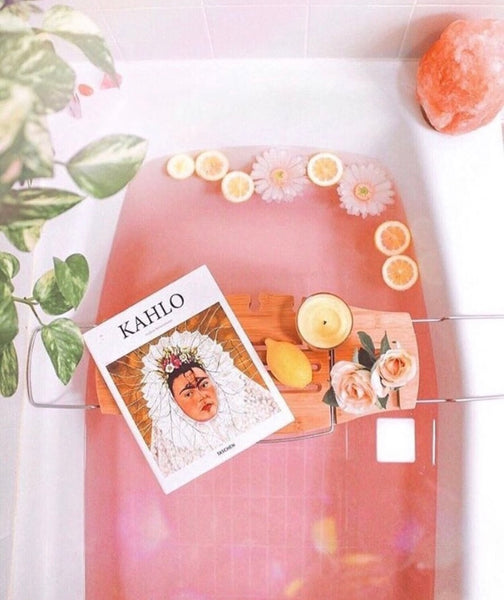 Picture of a white bathtub with pink water and fruits within the bath and a Harlem Candle Company candle burning
