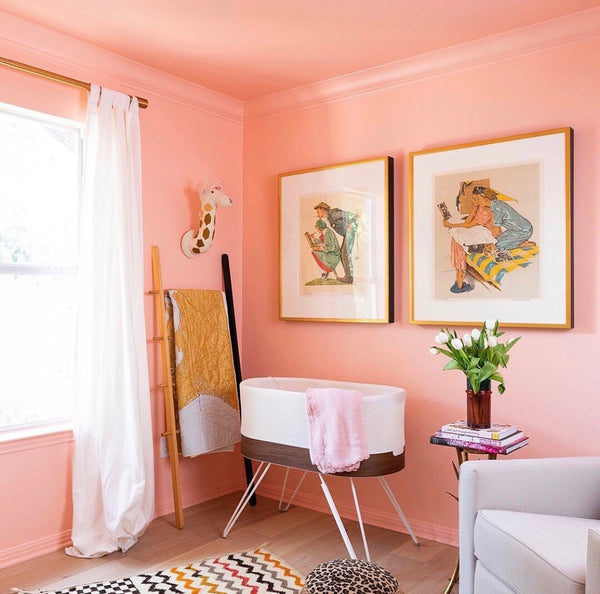 Clare Paint instagram photo of pink walled nursery with white curtains, colorful rug and two square modern art wall hangings.