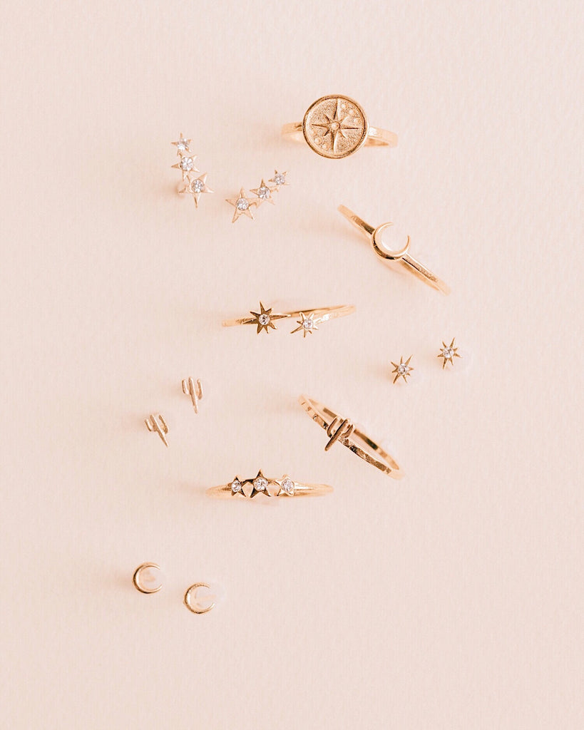 Dainty gold star and moon stacking rings photographed standing up on a pink background