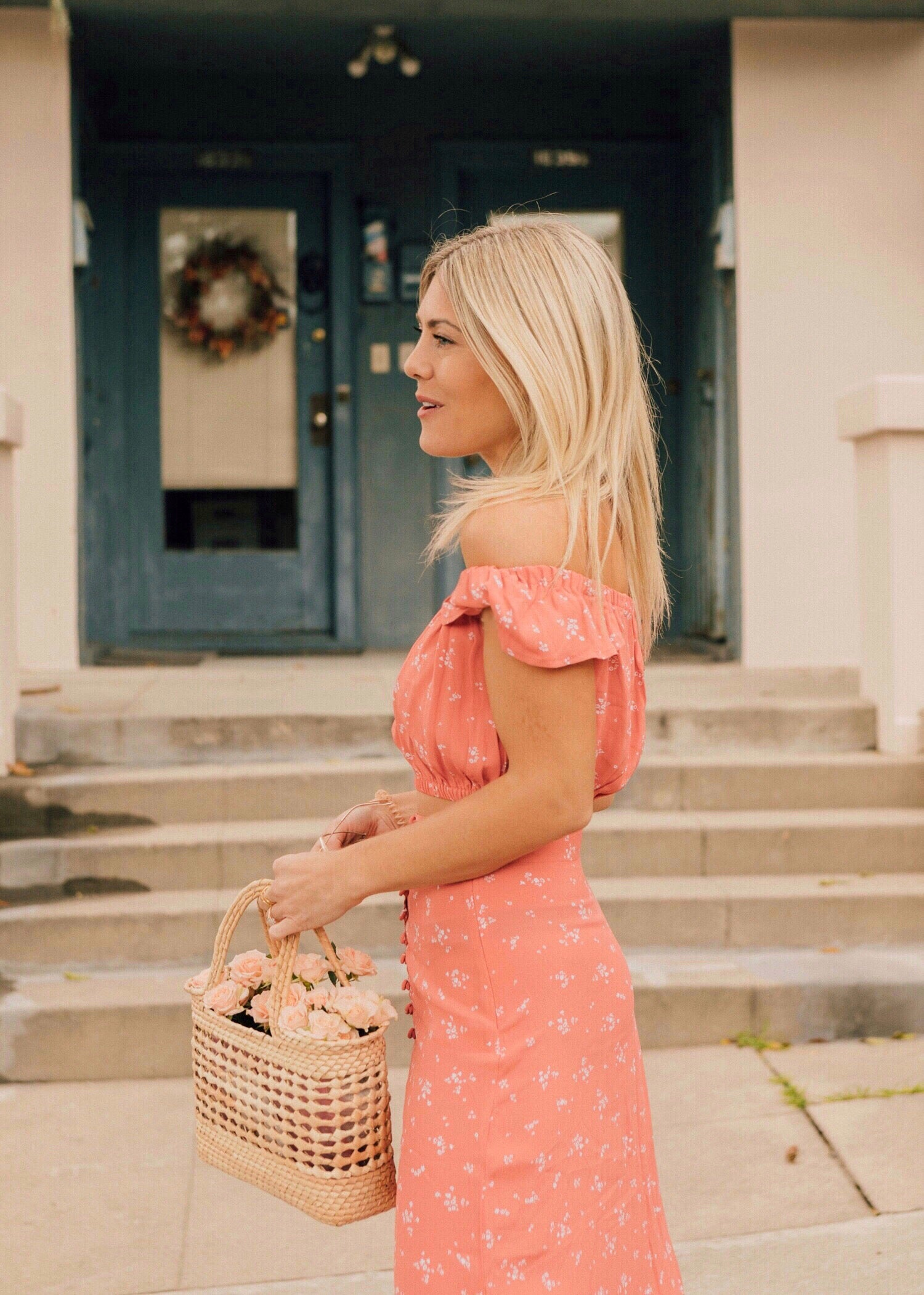 Katie Dean in two-piece floral, pink Spring outfit holding basket bag of pink flowers.