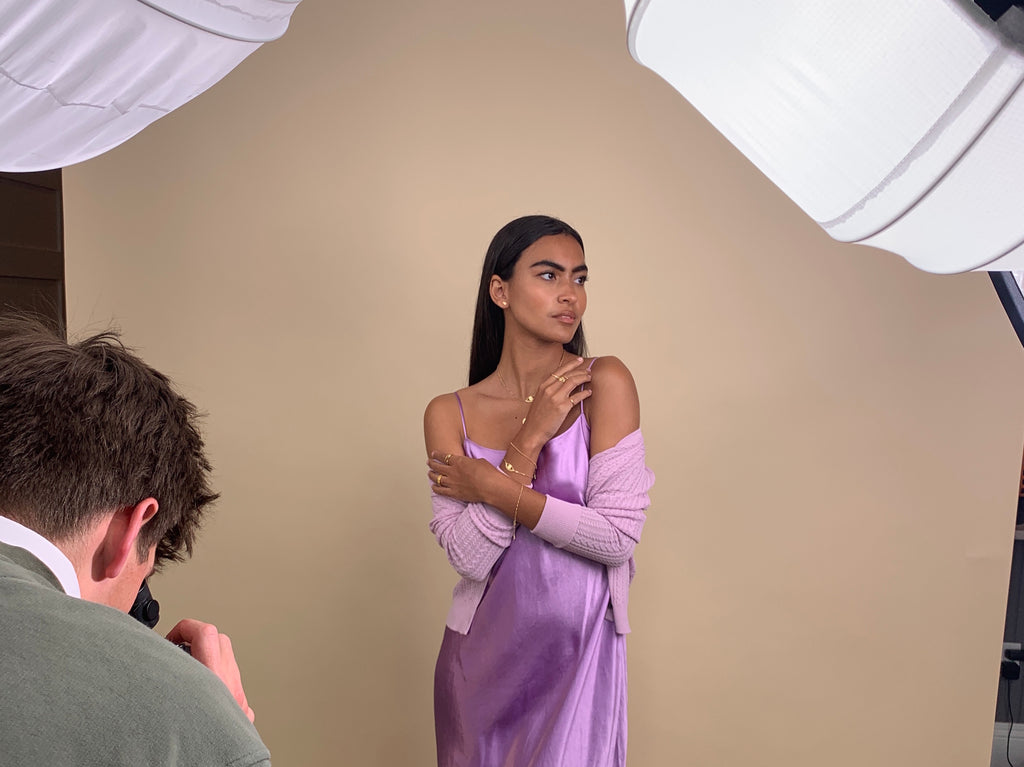 Image of a model posing with a pastel purple dress and cardigan and gold dainty stacking rings, bracelets and earrings on with a photographer taking a photo,Katie Dean Jewelry behind the scenes.