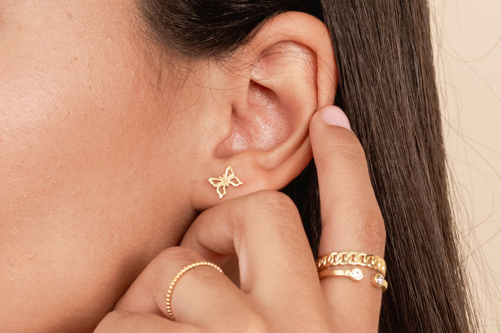 Dainty gold Butterfly Studs by Katie Dean Jewelry as seen on a model with her finger touching her ear wearing dainty gold stacking rings, handmade in the USA.