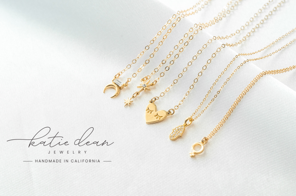 Dainty gold necklaces on white satin with moon, little dipper, heart, female symbol necklaces, Katie Dean Jewelry