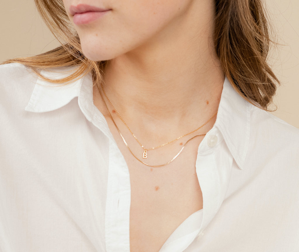 Picture of a model wearing the dainty gold necklaces, featuring the Initial Necklace and Herringbone Chain Necklace, handmade in America by Katie Dean Jewelry