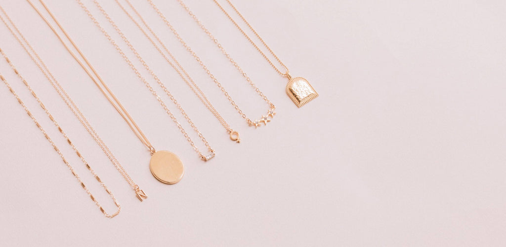 Dainty handmade gold necklaces photographed on a pink background by Katie Dean Jewelry. Made for a minimalist who likes to layer their jewelry.