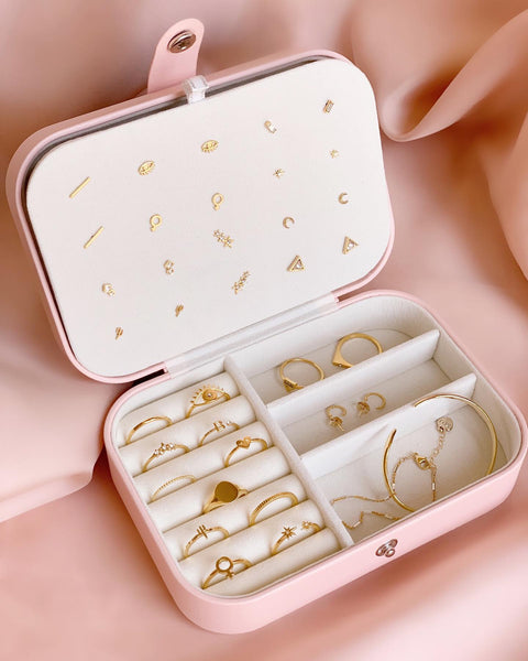 Inside of a pink jewelry case with a white suede interior and golden dainty earrings, rings, necklaces and bracelets organized inside