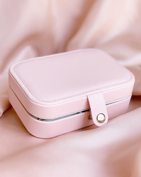 Outside of a pink jewelry case with a pink satin background