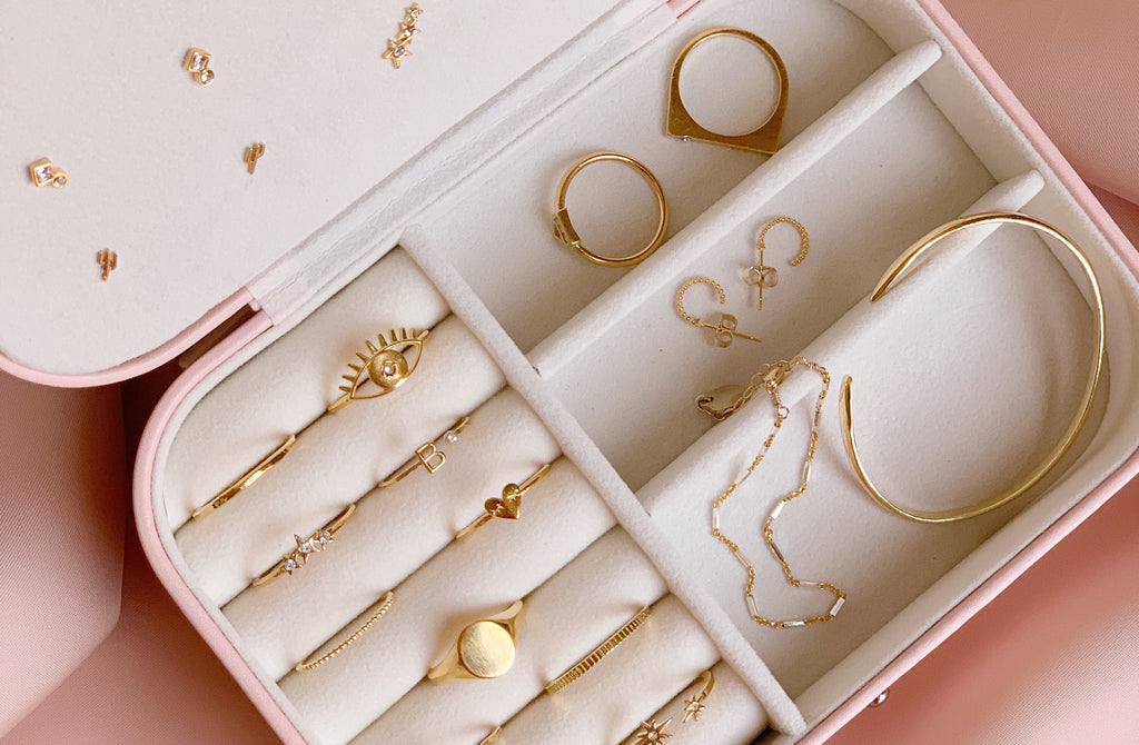 Katie Dean jewelry box, carrying case, filled with dainty hypoallergenic gold earrings, gold stacking rings and delicate bracelets