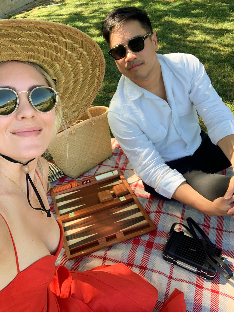 Katie Dean wearing a wide brim woven hat and red dress sitting on a checkered picnic blanket next to her husband with a wooden backgammon board game between them.