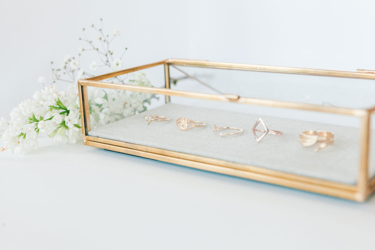 A gold-rimmed, glass display case with Katie Dean Jewelry rings displayed inside with white flowers next to the display.