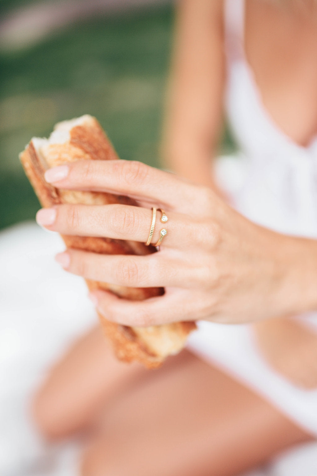 A women's hand holding a baguette and wearing Katie Dean Jewellery Two Gem Ring and Coin Ring