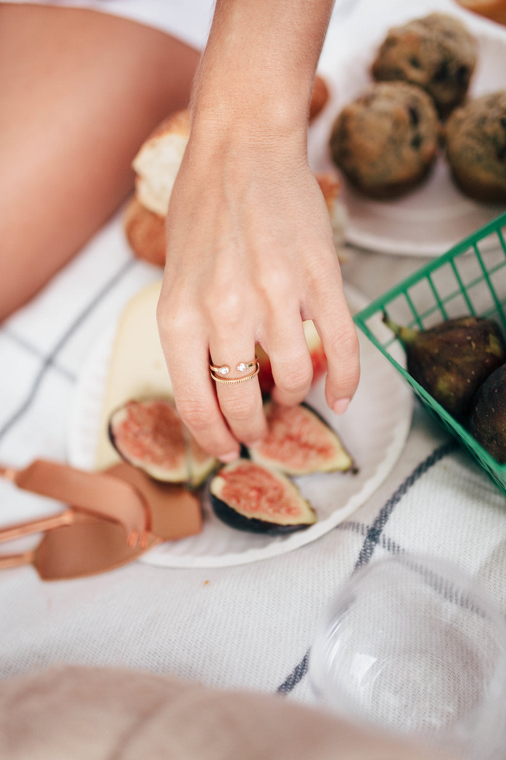 A women's hand reaching for a fig and wearing Katie Dean Jewellery Two Gem Ring and Coin Ring