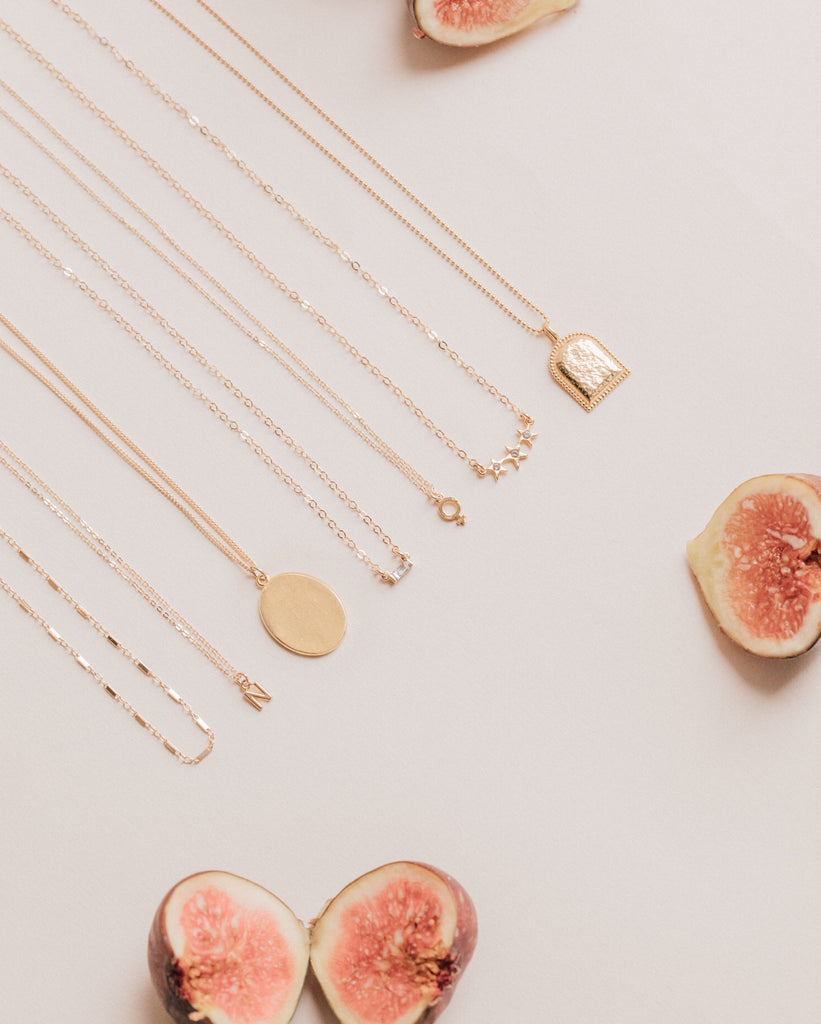 Katie Dean Jewelry dainty gold layering necklaces with figs on a pink background