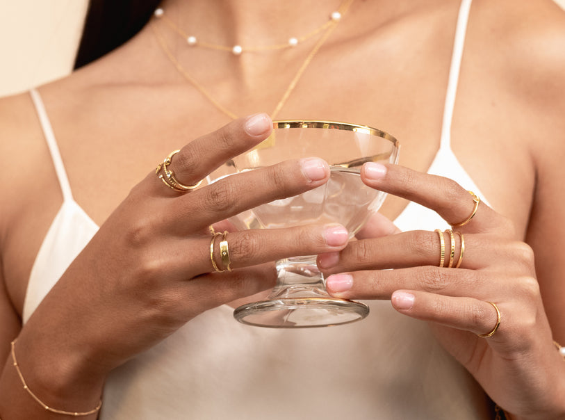 Katie Dean Jewelry dainty gold rings shown on a model holding a fancy glass spreading holiday cheer
