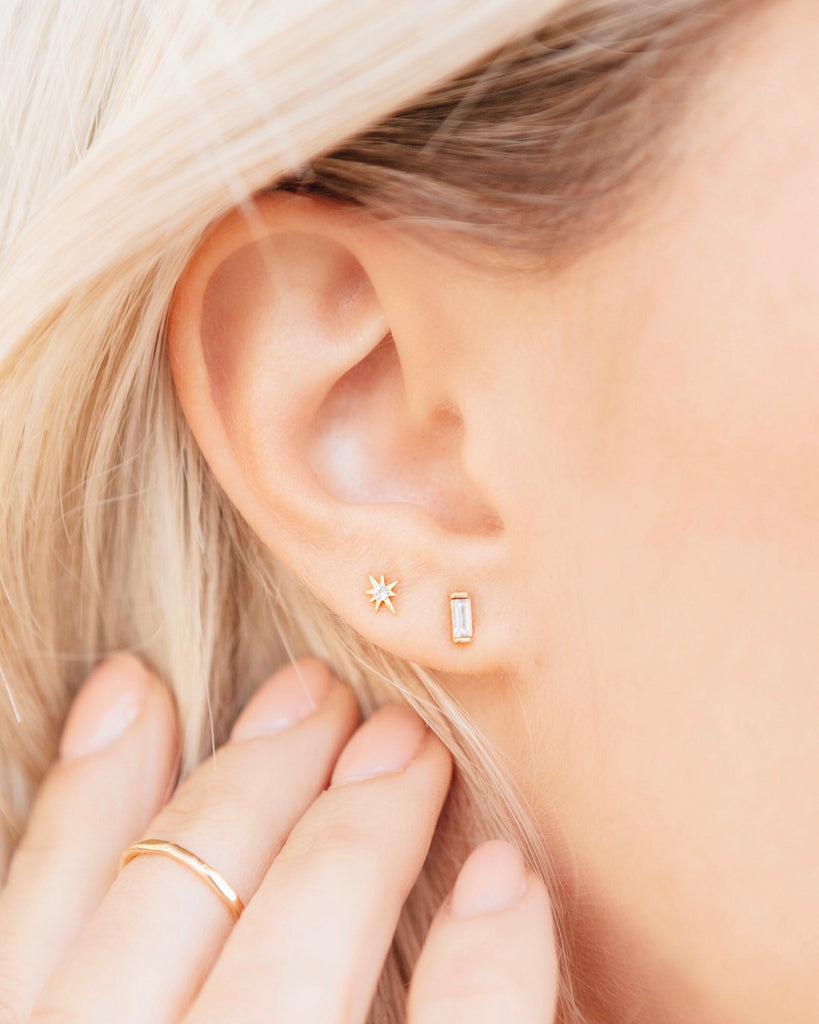 Picture of an ear with hair flowing around it on the left side, one star earring and one baguette earring showing as well as four fingers held up to the ear