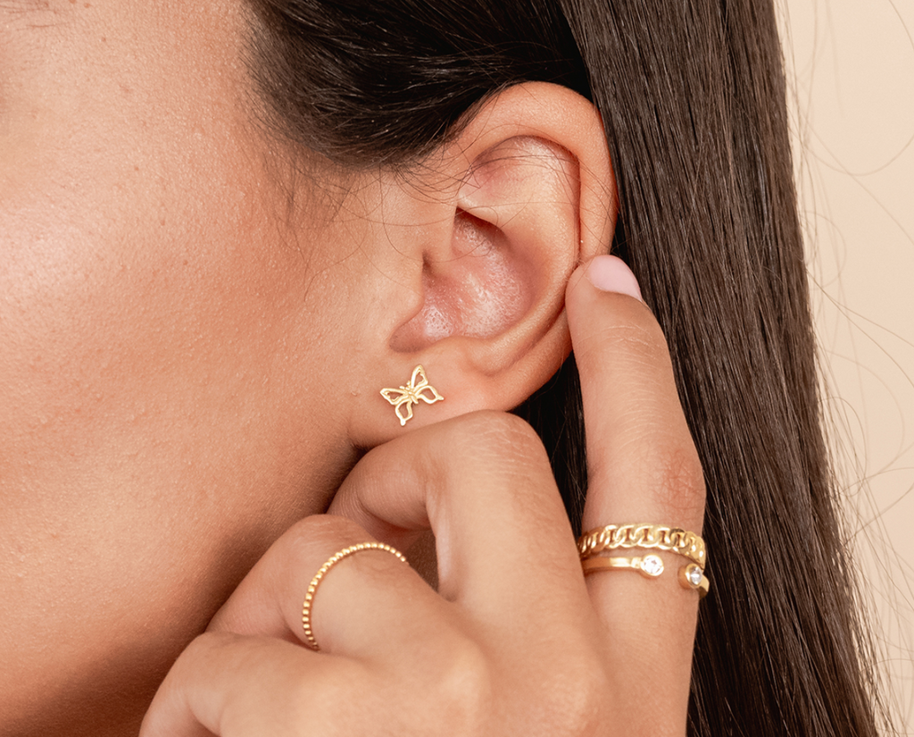 Model wearing the dainty gold Butterfly Earrings and dainty stacking rings by Katie Dean Jewelry