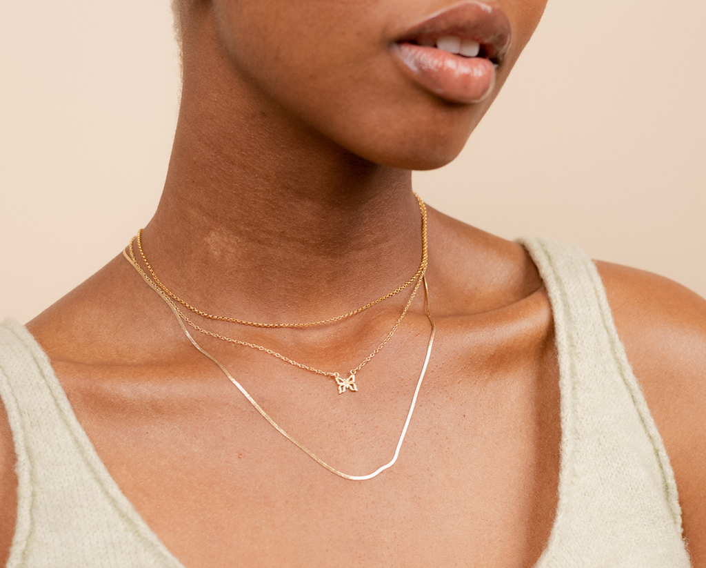 Model wearing the dainty gold Butterfly Necklace and Herrinbone Chain by Katie Dean Jewelry