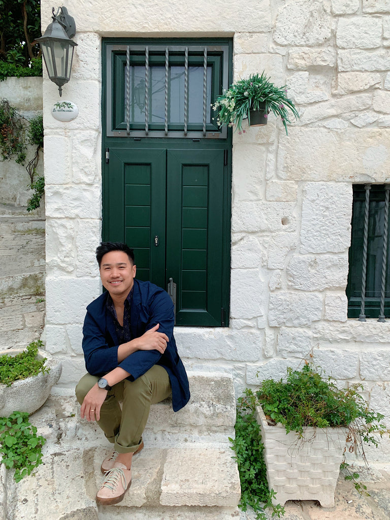 Puglia Italy trip 2019. My husband Jon sitting on front porch of the white washed home in Ostuni with forest green door and lantern