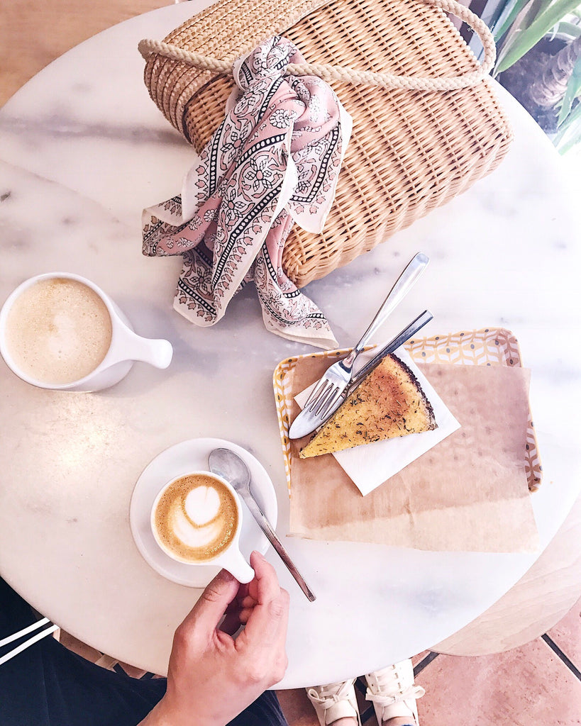 Onna Coffee, Barcelona Spain white marble table with cappucino and polenta cake on plates and wicker purse.