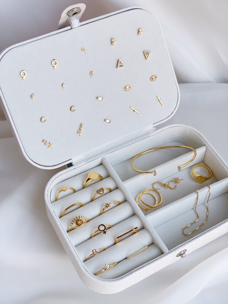 white jewelry carrying case with dainty Katie Dean Jewelry gold jewelry pieces in it
