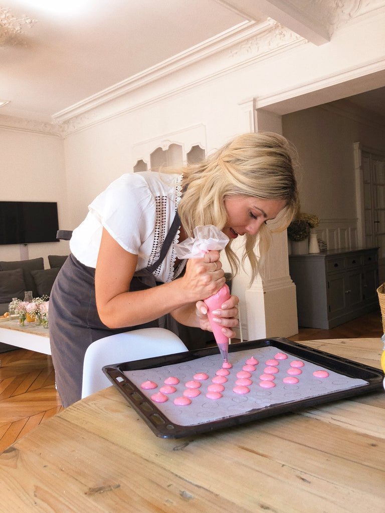Katie Dean wearing an apron in a Paris kitchen squeezing out pink French Macaron paste on to a baking pan.