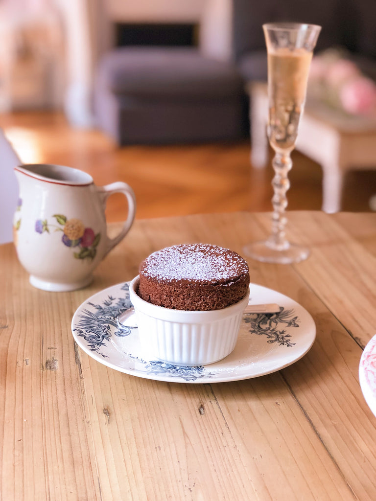 The freshly bakes Chocolate Souffle in a white dish and on top of a vintage plate with blue design.