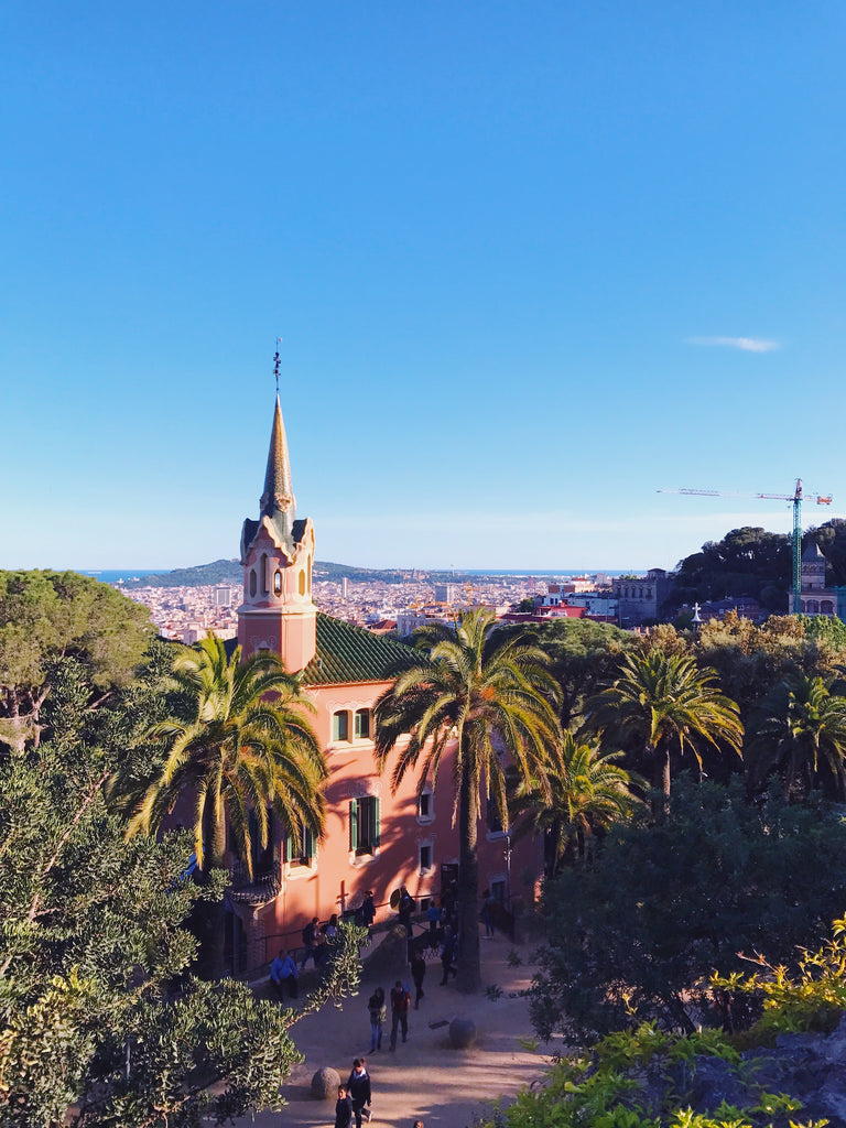 View of Barcelona from Park Guell. Showing a blue clear sky, palm, trees and a stunning pink building with a pointed steeple.