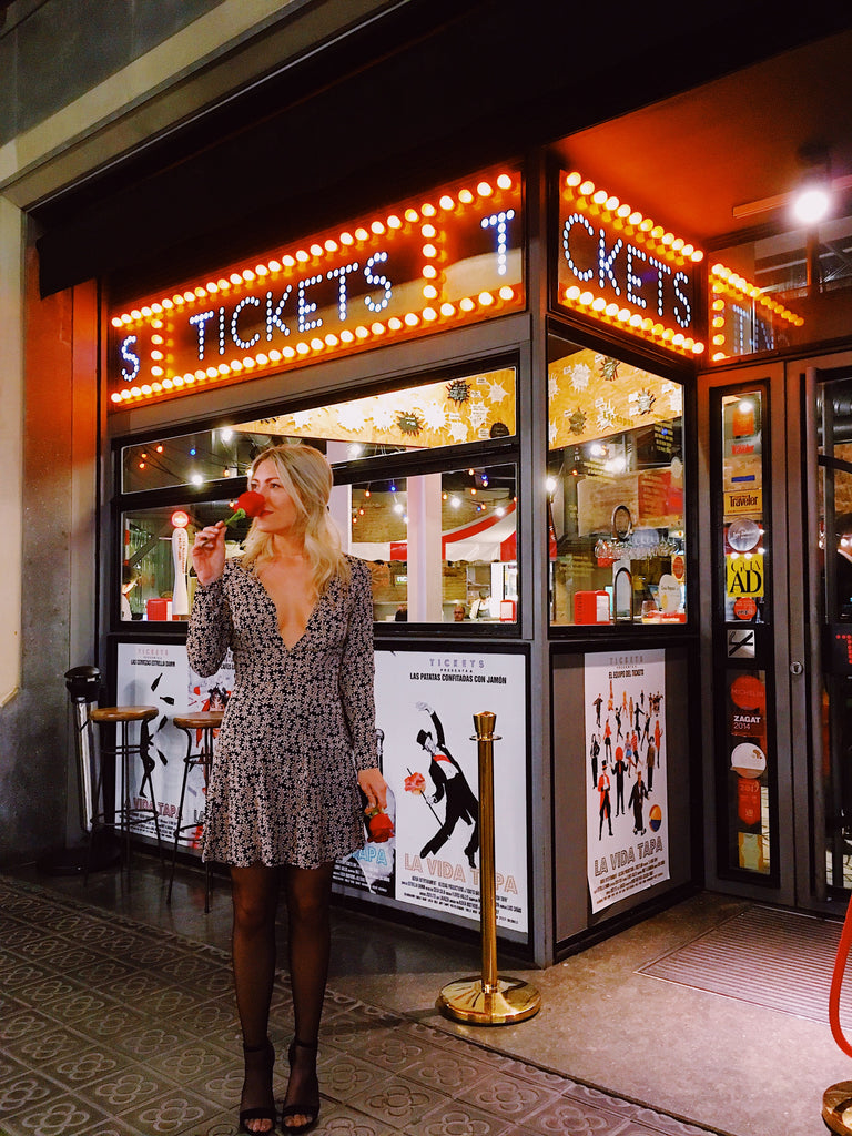 Katie Dean holding a rose and wearing a black and white mini dress, standing in front of Tickets Restaurant in Barcelona Spain. Large lit up sign saying tickets behind Katie.