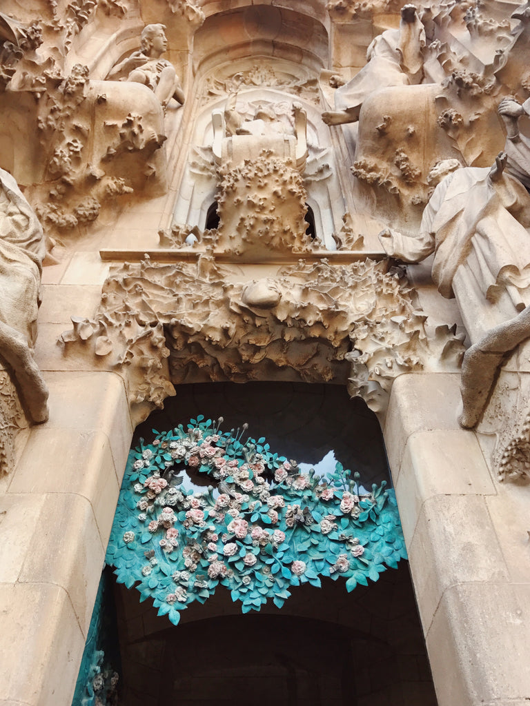 Portion of La Sagrada Familia church in Barcelona Spain with a stone and metal art installation in a archway with green and pink colors showing a rose bush.