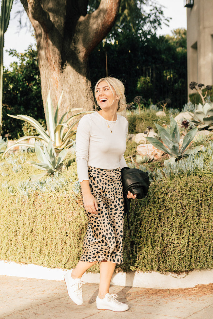 Katie Dean, founder of Katie Dean Jewelry, in a leopard print skirt, white tennis shoes and a white long sleeve shirt smiling and wearing her dainty gold jewelry while walking on a sidewalk in Los Angeles.