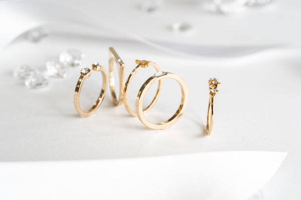 Katie Dean Jewelry gold dainty stacking rings standing up against a white background
